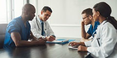 Physician executives gathered around a table in a conference room