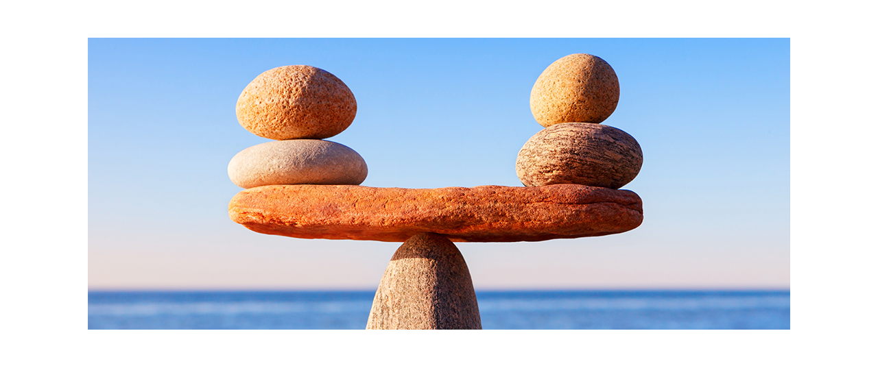 Seesaw made of stone balancing with two smaller stones
