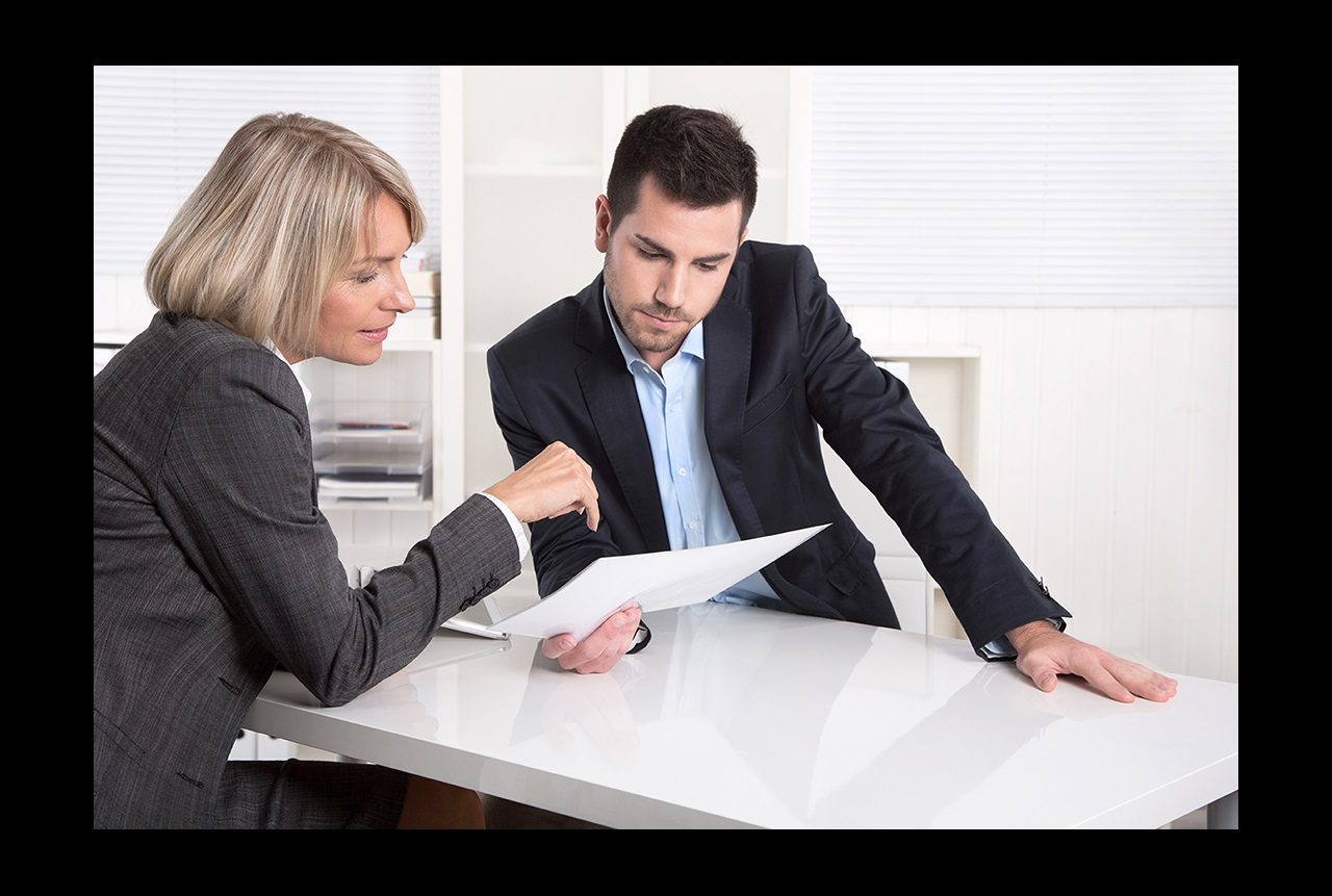 A man and woman in business suits sit at a table reviewing a document