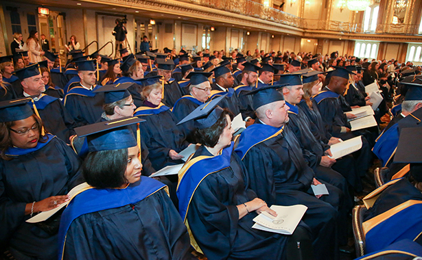 Group of individuals seated with caps and gowns at Fellow induction ceremony